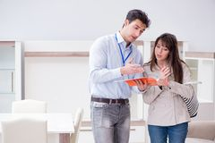 The salesman explaining to woman customer at furniture store. Salesman explaining to women customer at furniture store Stock Image