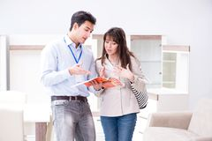 The salesman explaining to woman customer at furniture store royalty free stock image