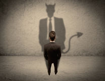 Salesman facing his own devil shadow Royalty Free Stock Photography