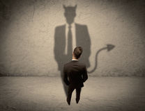 Salesman facing his own devil shadow Stock Images