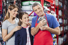 Salesman And Family Looking At Rabbit In Store. Happy salesman and family looking at cute rabbit in pet store stock photos