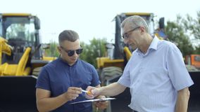 Buyer sign document about buying tractor. Salesman and farmer standing outdoors at the background of tractor. Buyer signing successful agreement about buying of stock footage