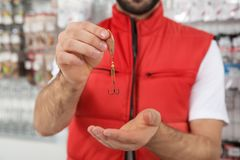 Salesman with fishing hook in sports shop. Closeup stock image