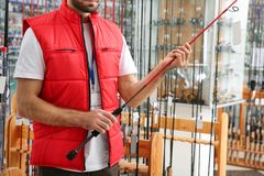 Salesman with fishing rod in sports shop. Closeup stock photos