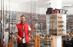 Salesman with fishing rod in sports shop. Space for text stock images