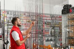 Salesman with fishing rods in sports shop. Space for text stock images