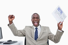 Salesman with the fists up while holding a graph. Victorious salesman with the fists up while holding a graph against a white background stock image