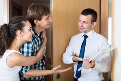 Salesman forcing family couple. Salesman in hall forcing family couple to buy subscriptions stock photo