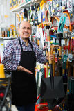 Salesman with garden tools in store Royalty Free Stock Images