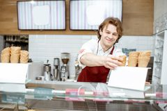 Salesman getting waffle cone for the ice cream in the shop. Handsome smiling salesman taking waffle cone while making ice cream for the client in the modern stock image