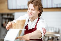 Salesman getting waffle cone for the ice cream in the shop. Handsome smiling salesman taking waffle cone while making ice cream for the client in the modern stock photography