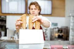 Salesman getting waffle cone for the ice cream in the shop. Handsome salesman taking waffle cone while making ice cream for the client in the modern pastry shop royalty free stock images