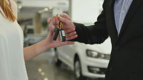 The salesman give the car keys to the buyer. The woman buys a car. She gives a credit card to the salesman. The guy takes a card and gives the car`s keys to the stock video