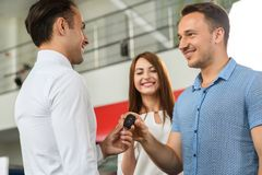 Salesman gives new keys to client from new car. Couple is very happy royalty free stock image
