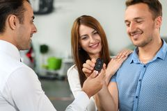 Salesman gives new keys to client from new car. Couple is very happy, they bought new car royalty free stock photos