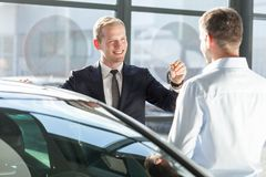 Salesman giving car key Royalty Free Stock Image