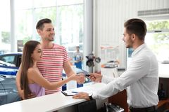 Salesman giving car key to happy couple. In salon stock images