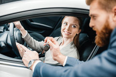 Salesman giving car key to smiling young woman sitting in new car Royalty Free Stock Images