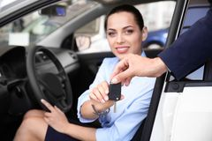 Salesman giving car key to woman on driver`s seat. Of automobile royalty free stock photos