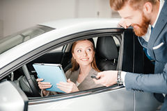 Salesman giving car key to young woman sitting in new car with digital tablet Royalty Free Stock Images