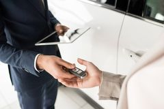 Salesman Giving Car Keys to Client. High angle close up of car salesman giving keys to client standing next to white luxury car, copy space Stock Image