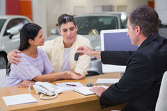 Salesman giving car keys to a couple. At new car showroom Stock Image