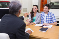 Salesman giving car keys to a couple. At new car showroom Royalty Free Stock Photo