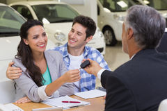 Salesman giving car keys to a couple Stock Image
