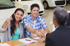 Salesman giving car keys to a couple Royalty Free Stock Images