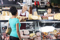 Salesman Giving Cheese To Female Customer At Counter. Smiling senior salesman giving cheese to female customer at counter in grocery shop Royalty Free Stock Photos