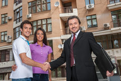Salesman giving handshake to property owners. Royalty Free Stock Photos