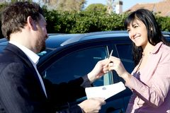 Salesman giving key of new car to happy woman Stock Image