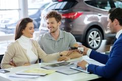 Salesman giving the key of the new car to a young couple at the dealership  showroom. Stock Images