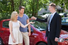 Salesman giving key to couple by car Royalty Free Stock Photography
