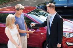 Salesman giving key to couple by car Stock Photo