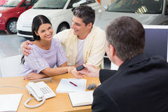 Salesman giving key to a smiling couple. At new car showroom Stock Image
