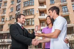 Salesman giving keys to property owners. Royalty Free Stock Photos
