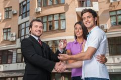 Salesman giving keys to property owners. Stock Images