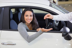 Salesman giving keys to a smiling woman Stock Image