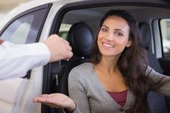 Salesman giving keys to a smiling woman Stock Photos