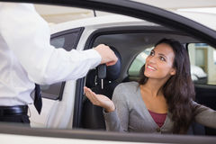 Salesman giving keys to a smiling woman Royalty Free Stock Images