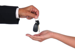 Salesman giving keys to woman. Closeup of a car salesman dropping keys into a woman's waiting hand. Horizontal format showing hands only over a white background stock photography