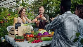 Salesman giving organic products to customers in greenhouse farm market. Friendly salesman and his wife are giving organic products to customers in greenhouse stock video footage