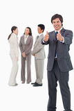 Salesman giving thumbs up with colleagues behind him Royalty Free Stock Images