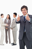 Salesman giving thumbs up with team behind him Royalty Free Stock Photography