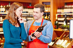 Salesman giving woman advice on buying wine. Salesman giving elderly women advice on buying bottle of red wine Royalty Free Stock Images