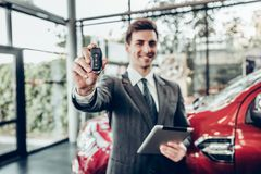 Salesman in grey suit holding car key on red car background. Focus on key royalty free stock photography