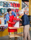 Salesman Guiding Man In Selecting Tools At Store Royalty Free Stock Image