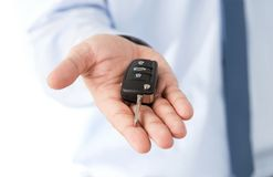 Salesman hand giving a key to a dream car. Close up of dealers hand giving a key to a dream car isolated on white background with copy space Royalty Free Stock Images