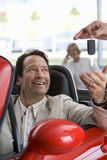 Salesman handing key to satisfied male customer sitting in red convertible in car showroom, smiling Stock Images